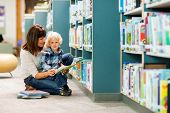 Portrait of boy with teacher reading book by bookshelf in library
