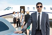 Portrait of confident businessman with airhostess and pilot greeting businesswomen against private j