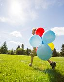 stock photo of helium  - Full length side view of young boy with colorful helium balloons walking in park - JPG
