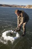 Man In Camo Chopping Hold In Ice With Axe Down