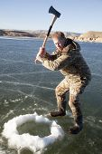 Man In Camo Chopping Hole In Ice With Axe Swing