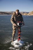 Man In Camo Drilling Hole In Ice Look Down