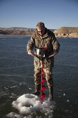 image of auger  - A man using an ice auger to drill a hole in the ice - JPG