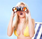 Young Woman In Bikini Looking Through Binoculars
