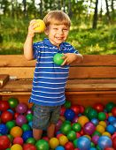Happy child playing with colorful plastic balls at playground.