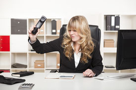 picture of slam  - Beautiful young blond businesswoman slamming down the phone in her office after an argumentative phone call or in frustration - JPG
