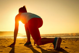 stock photo of sprinters  - Female athlete in powerful starting line pose at the beach - JPG