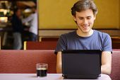 Happy Man Browsing Internet On A Laptop In A Restaurant