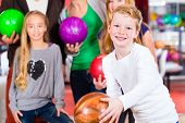 stock photo of health center  - Parents playing with children together at bowling center - JPG