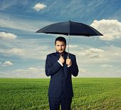 displeased businessman under black umbrella outdoors