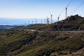 stock photo of tarifa  - Landscape with wind turbines hills and sea - JPG