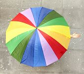 Woman hidden under multicolored umbrella and checking if it's raining