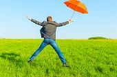 Businessman With Umbrella Jumping In A Field