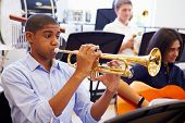 stock photo of trumpets  - Male Pupil Playing Trumpet In High School Orchestra - JPG