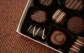 box of chocolates on brown woven surface