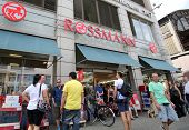 BERLIN, GERMANY - JUNE 11, 2014: Pedestrians walk past a Rossmann drugstore in  Berlin, Germany, on