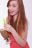 stock photo of vivacious  - Vivacious beautiful young teenager enjoying a party laughing at the camera while holding a cocktail in her hands with colorful extensions in a her long red hair - JPG