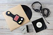 High angle shot of retro style music accessories. Items include: Vinyl LP, 45 rpm single, headphones, guitar case and a cassette tape. Horizontal format on a white wood surface.