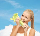 healtcare, food and diet concept - smiling woman biting piece of celery or green salad