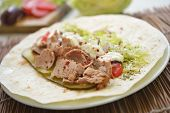 Making doner kebab with meat, vegetables, and yogurt