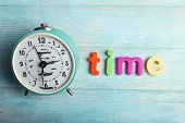 Time word formed with colorful letters on wooden background
