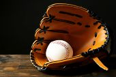 Baseball ball in glove on black background