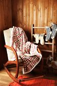 Rocking chair with plaid and book near wooden wall