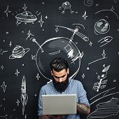 Tattoed Man Working With Laptop And Dreaming