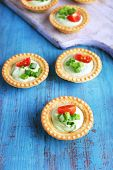 Tartlets with greens and vegetables with sauce on wooden tray on table
