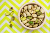 Pistachio nuts in wooden bowl on yellow and white cloth