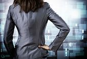 Rear view of businesswoman against digital background