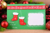 Handmade Christmas card with Christmas decorations on wooden background