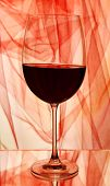 Red wine glass of wine on bright background