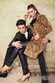 Young fashion man sitting on old factory ruin holding his lover on his leg.