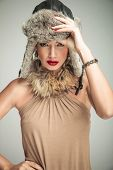 sexy beautiful woman in luxury clothes and fur hat standing with one hand on hip and one holding her hat