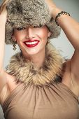 young beautiful woman laughing while holding hands on her fur hat