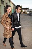 Full length picture of a young fashion couple walking forward, holding hands.