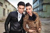 Close up picture of a young fashion couple posing near old factories, both holding hands in pockets.