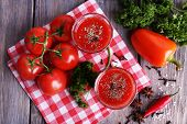 Tomato juice in glasses and fresh vegetables on napkin on wooden background