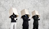 Unrecognizable businesspeople wearing carton box on head