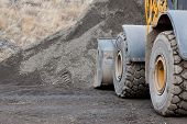 pic of wheel loader  - Large wheels and the bucket of a construction loader up against a pile of gravel at a job site - JPG
