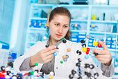 young woman scientist working at the laboratory. Model of molecule on a  hand