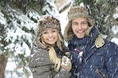 Winter portrait of happy loving couple smiling in snowfall.