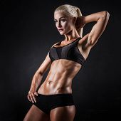 image of muscle builder  - Beautiful athletic woman showing muscles on dark background - JPG