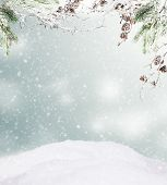 Snowy winter hill with spruce branches and free space for text
