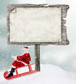 Empty wooden board with copy-space for text with Santa Claus on sledge