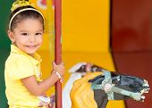 Cute small mixed race girl riding a colorful carousel