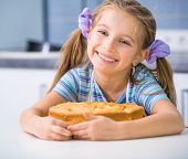 little happy girl showing apple pie that she baked