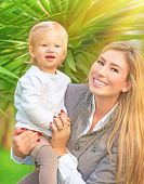 Portrait of happy cute mother with little baby in tropical park in sunny day, having fun outdoors, healthy lifestyle, love and childcare concept