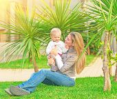 Young happy family having fun on backyard, mother with little daughter sitting on green grass and enjoying nice sunny day, love concept